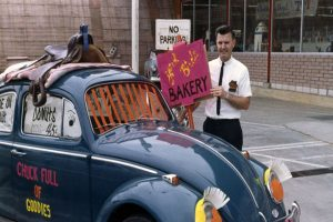 Dick Baker with a VW Beetle promoting the Yard Birds Bakery