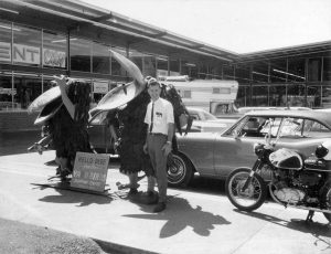 Dick Baker in front of the old Chehalis store with Yard Birds and a motorcycle.