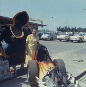 Ann Helena posing with a Yard Birds statue and the sponsored dragster